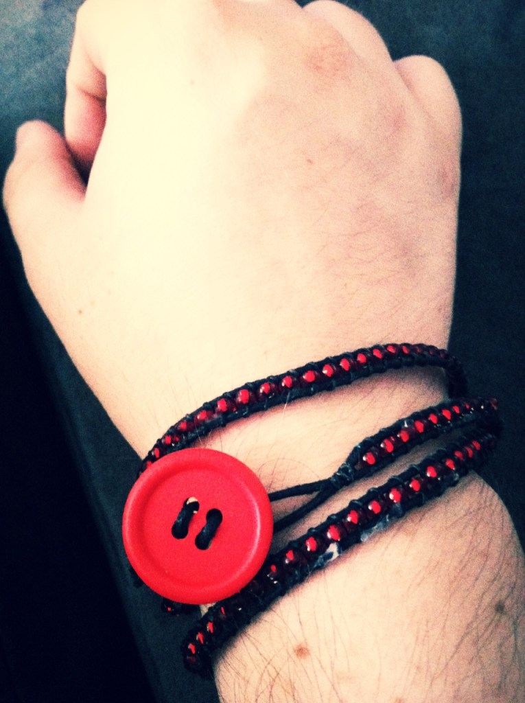 black faux-leather wrapped with red beads and a red wooden button to fasten