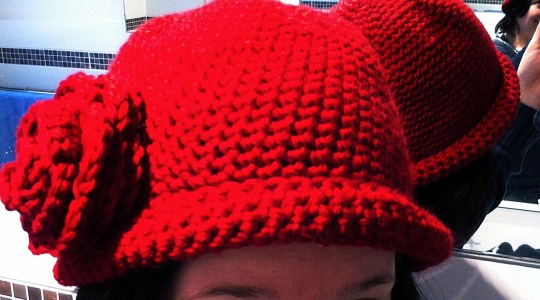 red crochet cloche hat with large crochet flower on the side