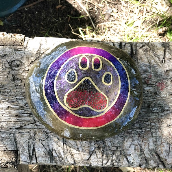 Natural rock with animal paw design in purple and pink front view