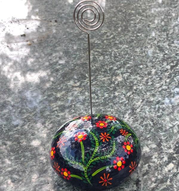 round memo or desk top photo holder with flower design against a dark background