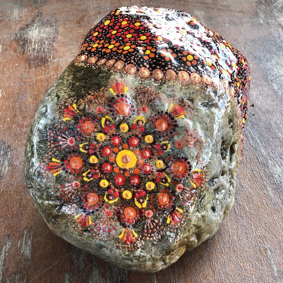 Natural rock door stop with orange, red, yellow and copper colour mandala design