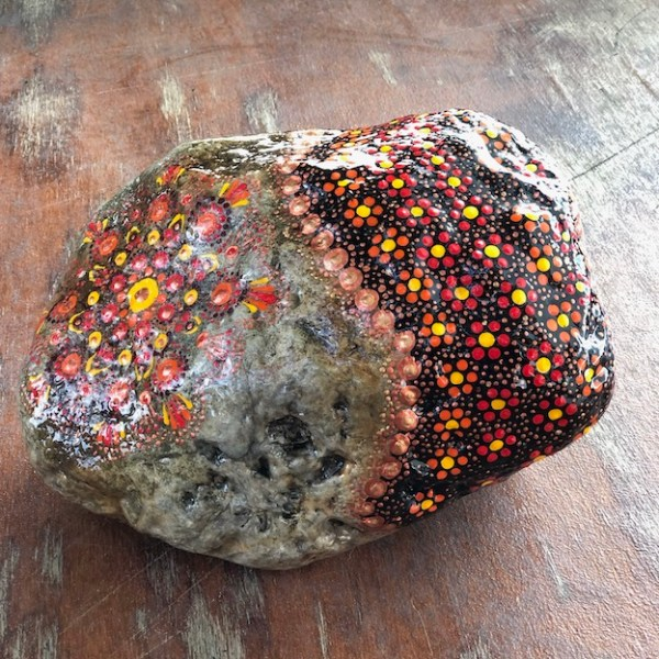 Natural rock door stop with orange, red, yellow and copper colour mandala design left side