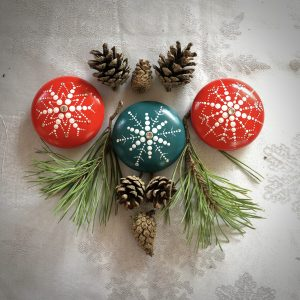 three snowflake stones in teal and red on a table