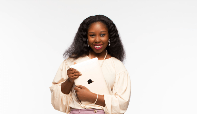 African American female smiling while holding apply laptop, wearing cream shirt, long pearl necklace, lavender bottom, dangle earrings, dark brown natural Curly hair. DIY beauty products owner Victoria Smith.