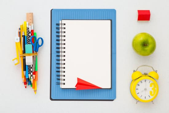 Side business ideas for teachers: blank spiral notebook, alarm clock, and school tools.