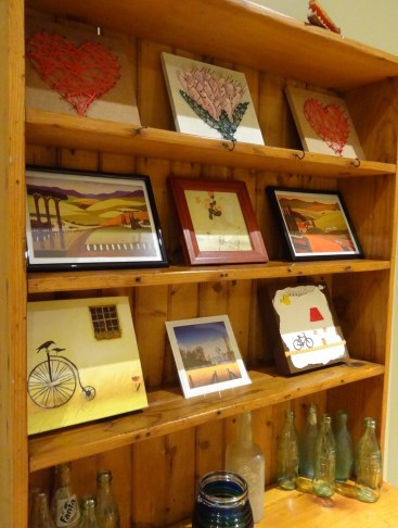 Various small artworks displayed on shelf