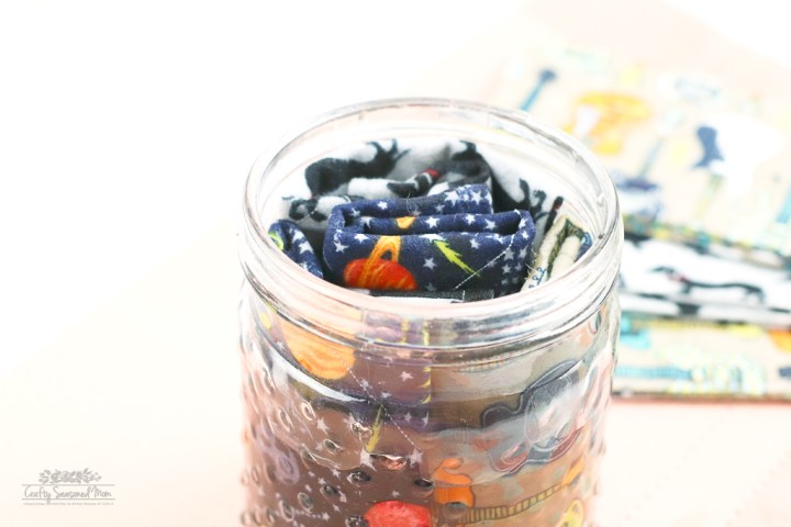 DIY Reusable Disinfecting Wipes Solution in large glass container with flannel squares close up