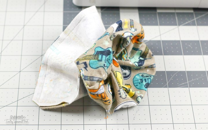 guitar print flannel fabric sewn together turned inside out for the DIY Reusable Disinfecting Wipes on a grey cutting mat