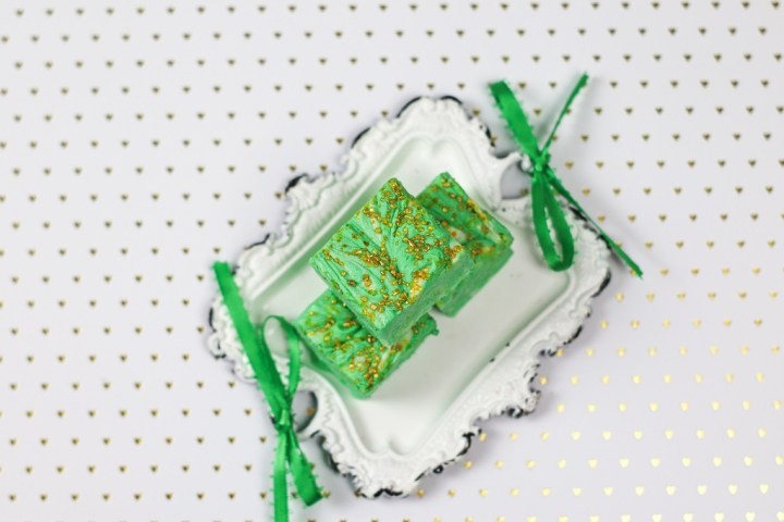 square of green fudge with gold sprinkles on a small white metal tray with green ribbon on a white and gold dot paper