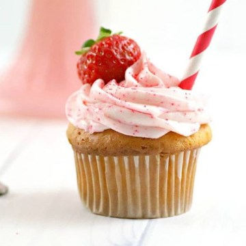 cupcake with pink frosting with fresh strawberry and red and white straw in front of a pink cake stand for Homemade Strawberry Soda Infused Cupcakes Recipe
