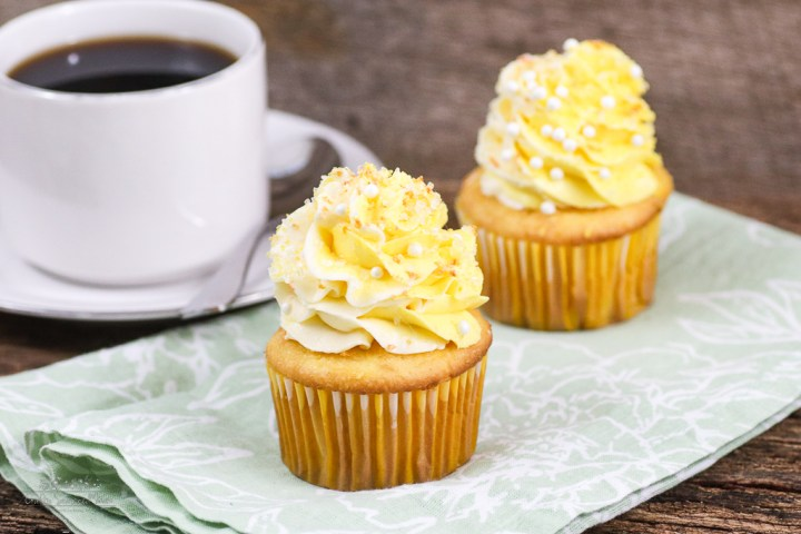 Double Lemon Jello Pudding Poke Cupcakes Recipe 2 cupcakes on a green napkin next to a cup of coffee in a white cup on a white saucer with a silver spoon