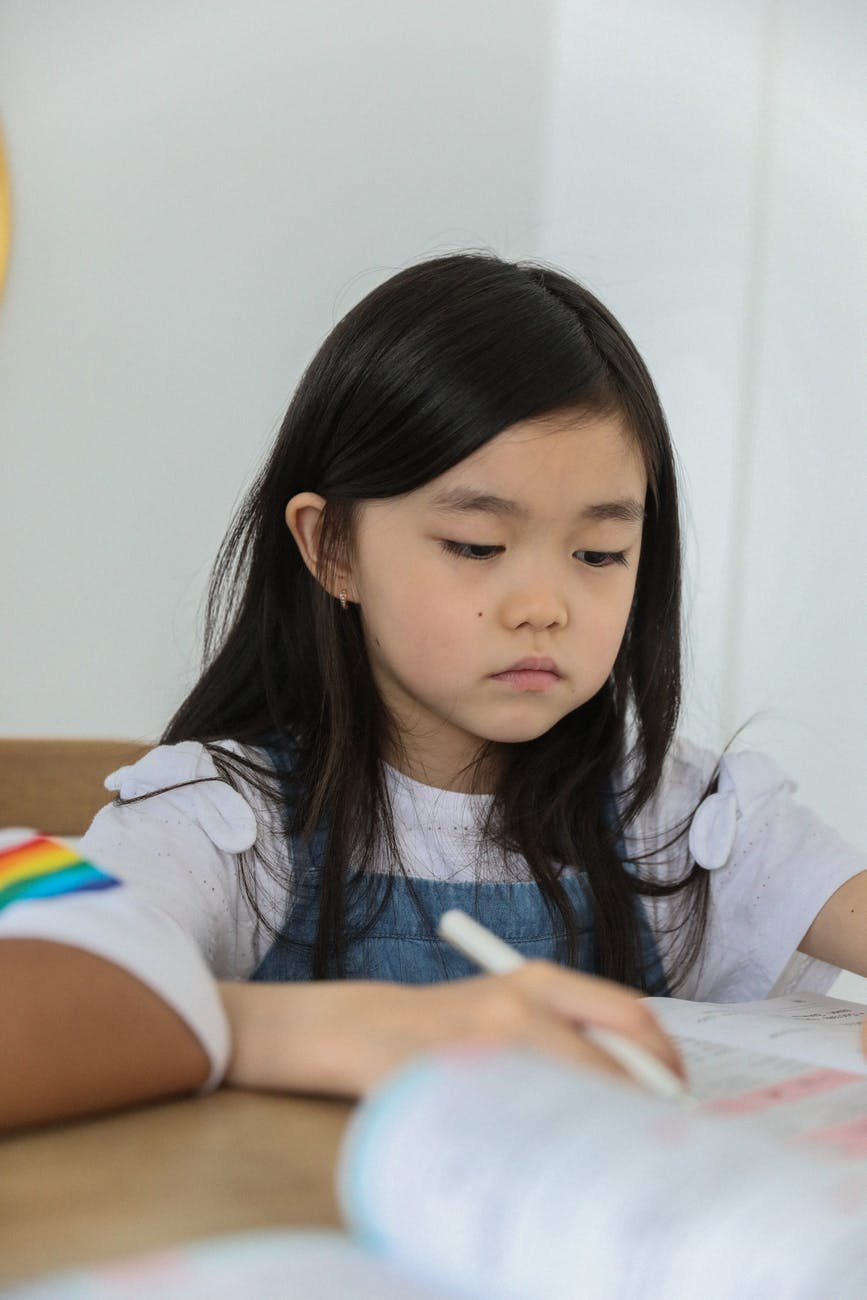 focused ethnic schoolgirl doing studies at table in classroom