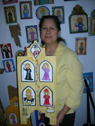"Theresa Montoya shows off one of husband Richard's retablos depicting Beatles songs, ""For the Benefit of Mr. Kite."" (Craig Davis/Craigslegztravels.com)"