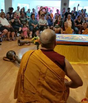 The monks are seated around the mandala with horns, drums and smbols; we are seated behind them — at Coral Springs Center For The Arts.