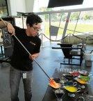 Richard Dextraze dips hot glass into assorted colors to begin the glassblowing process at Hollywood Hot Glass. (Craig Davis/Craigslegztravels.com)