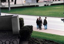 Viewed from the stockade fence on the Grassy Knoll, tourists in Dealey Plaza at the spot where President Kennedy was shot look back toward the former Texas School Book Depository. (Craig Davis/craigslegztravels.com)
