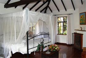Sovrum med vita väggar, mörka takbjälkar