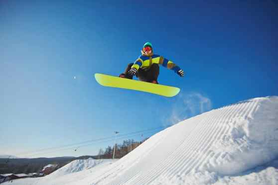 Snowbordist jumping on snow