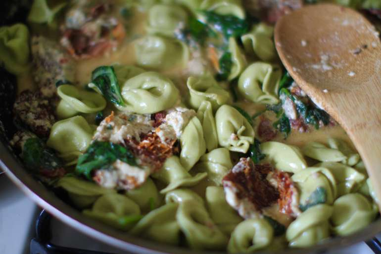 Sun-dried tomato basil tortellini with creamy spinach and cheese sauce.