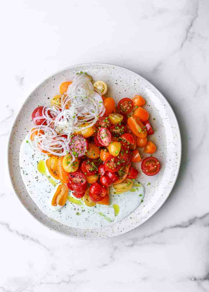 Tomato Salad with Buttermilk-Basil Dressing on a Plate with Chives and Shallot