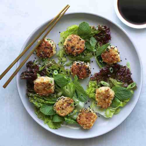 Meatballs on a plate with lettuce leaves, chopsticks and soy sauce on the side