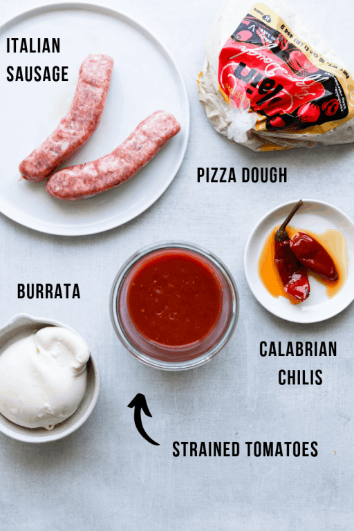 ingredients for pizza; pizza dough, sausage, sauce, burrata, chilis