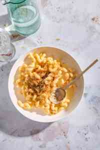 butternut squash mac and cheese topped with crispy sage breadcrumbs in a bowl with a gold spoon