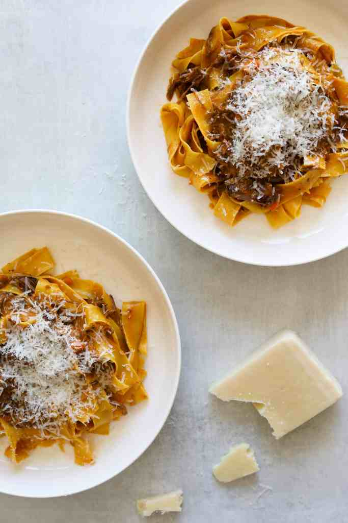 Two bowl of Short Rib Ragu with Pappardelle with parmesan cheese on top