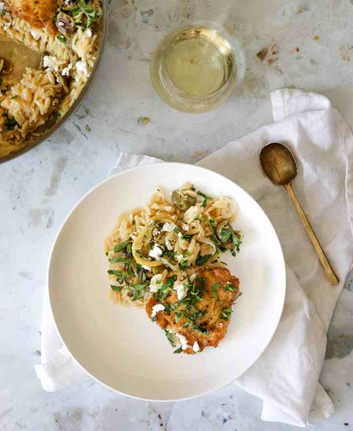 One-Pot Chicken with Orzo, Lemon, and Feta in a bowl with a glass of white wine