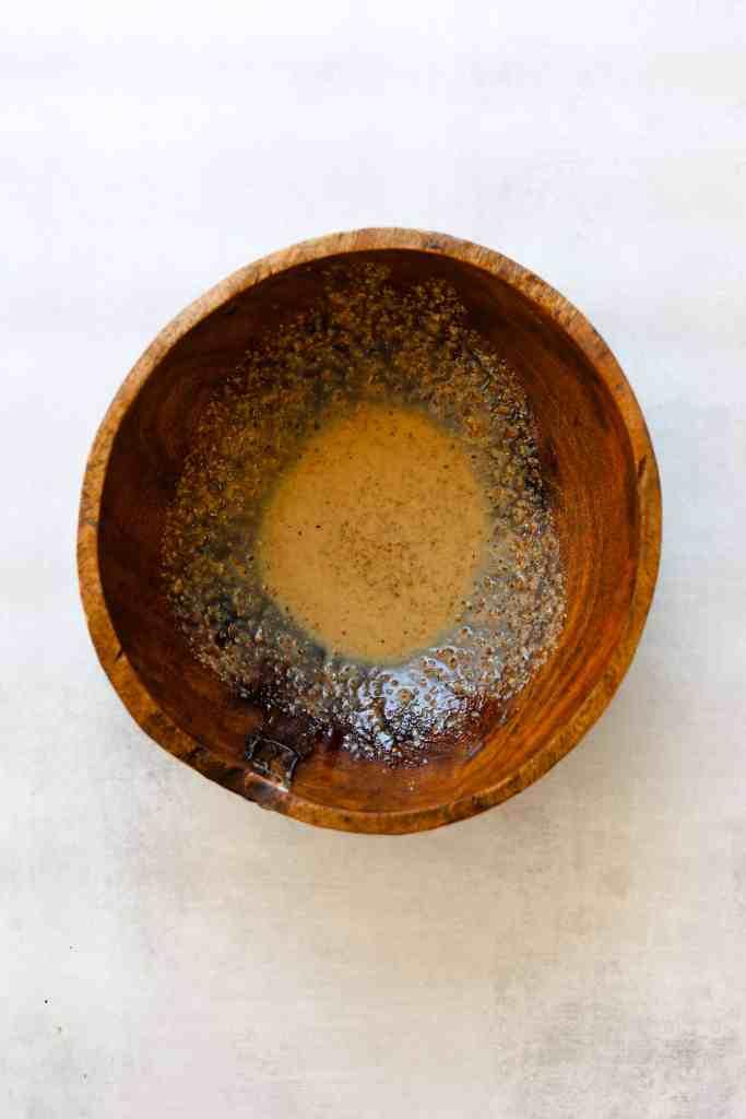 grainy mustard vinaigrette in a wooden salad bowl