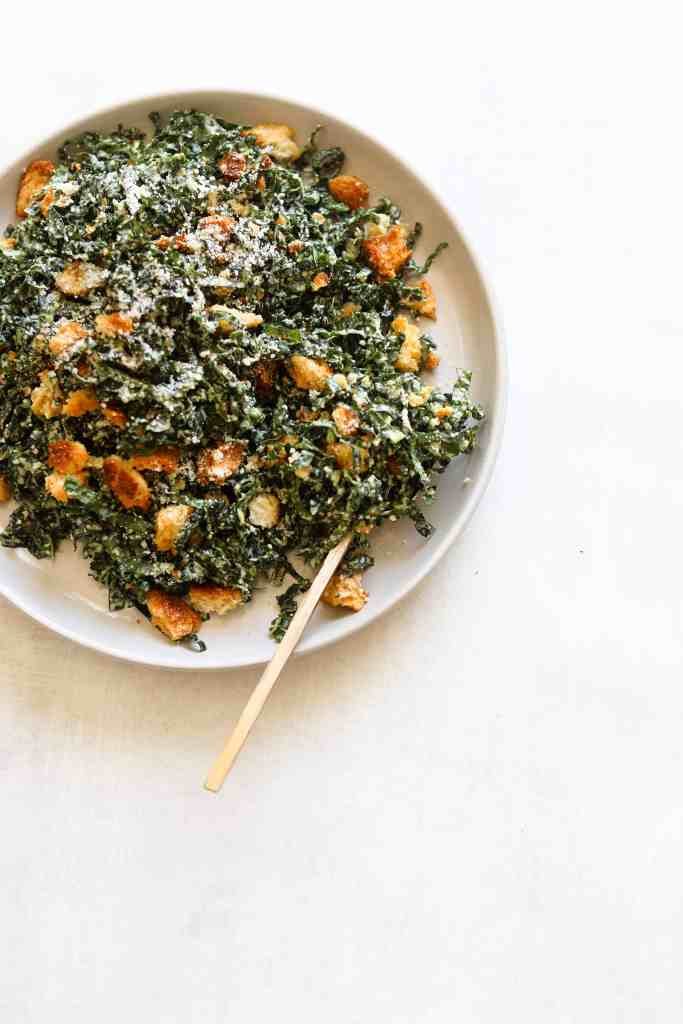 The Perfect Kale Caesar Salad on a white plate with a gold spoon