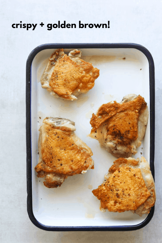 crispy seared chicken thighs on a baking tray