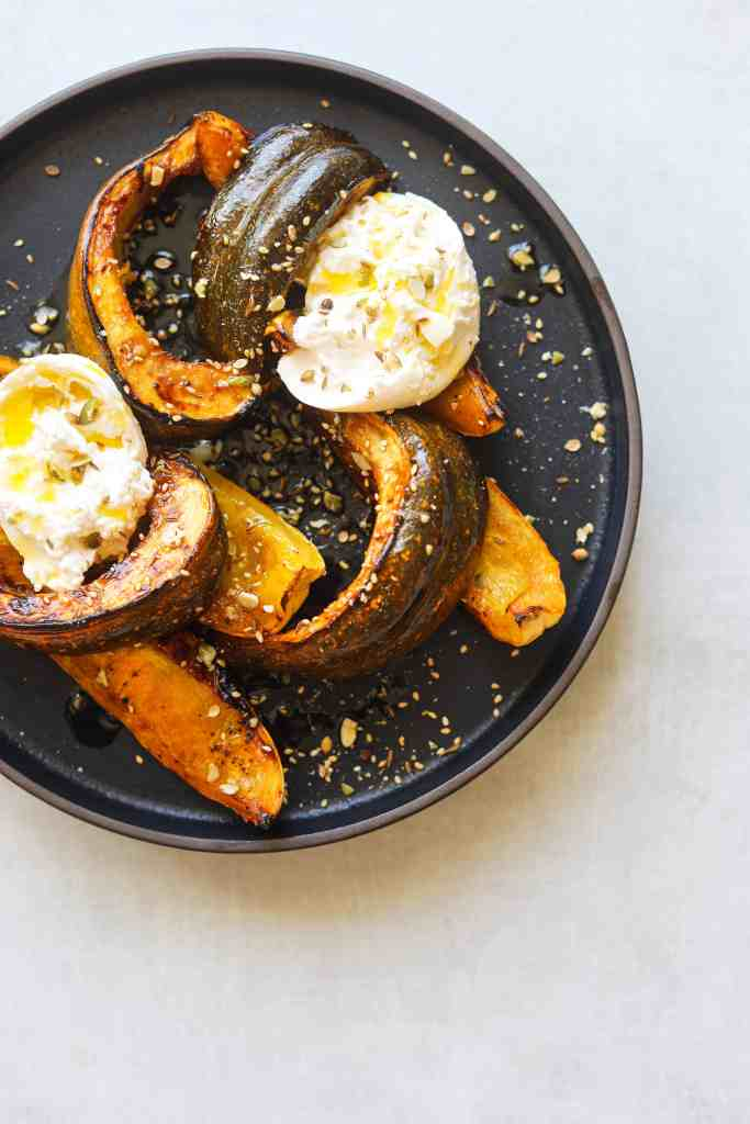 Honey Roasted Squash with Burrata and Pumpkin Seed Dukkah on a black plate