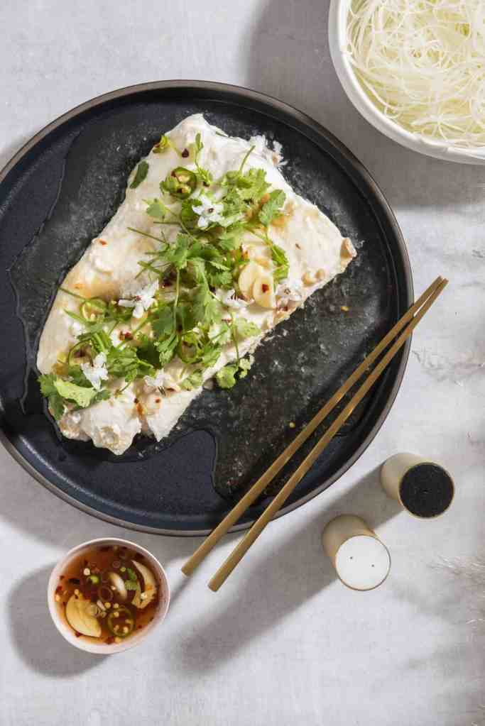 steamed fish on a black plate covered in cilantro and scallions with sauce on the side