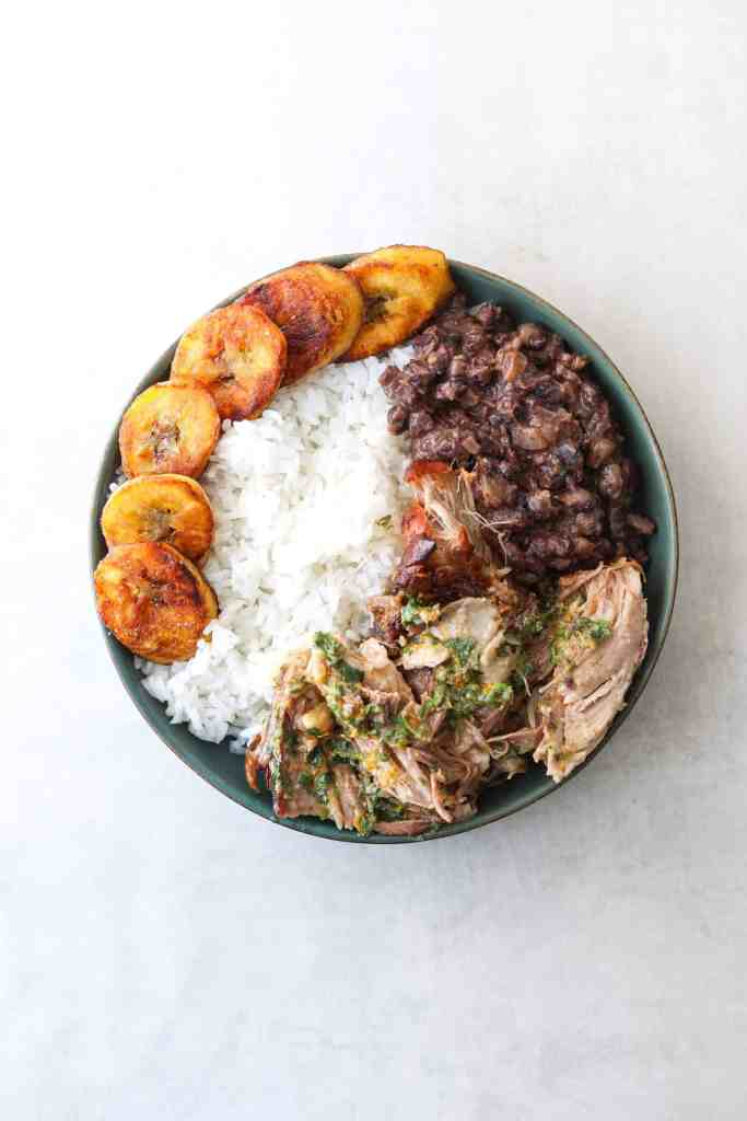A bowl of mojo pork, white rice, black beans and fried plantains