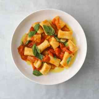 Ricotta Gnocchi with Quick Cherry Tomato Confit in a white bowl on a blue background