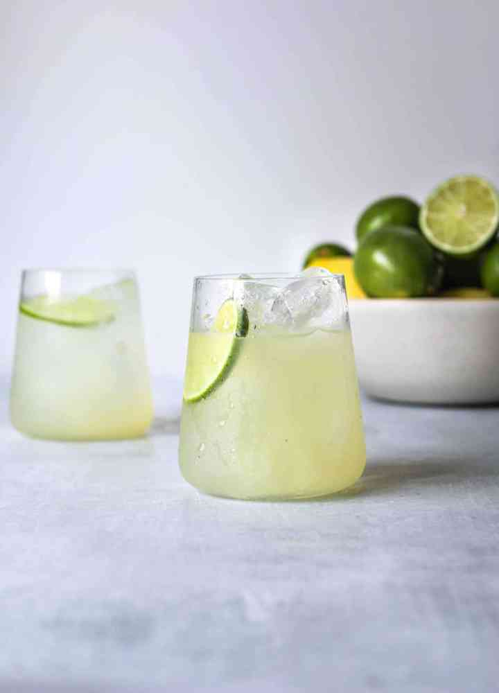 tTwo ice cold glasses of the perfect mezcal margaritas