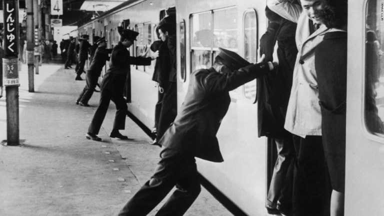 """Oshiya"" or ""pushers"" at Tokyo's Shinjuku station trying to pack as many passengers as possible into the carriages during rush hour in 1967. Photo credit: CNN"