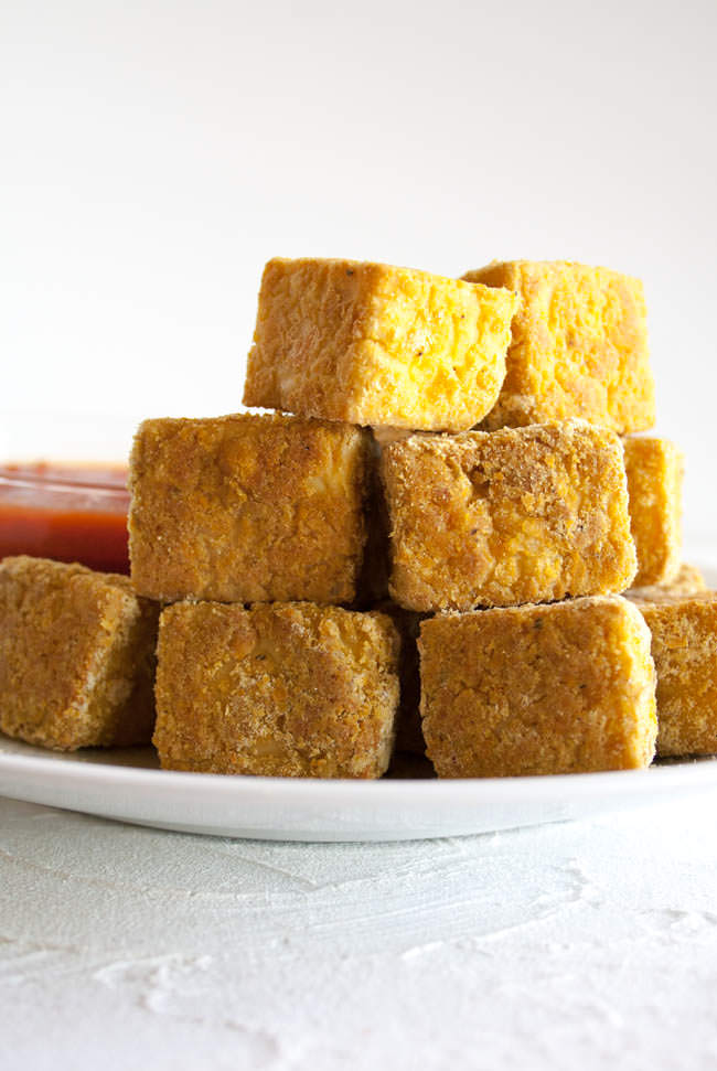 Baked Tofu Nuggets stacked on a plate.
