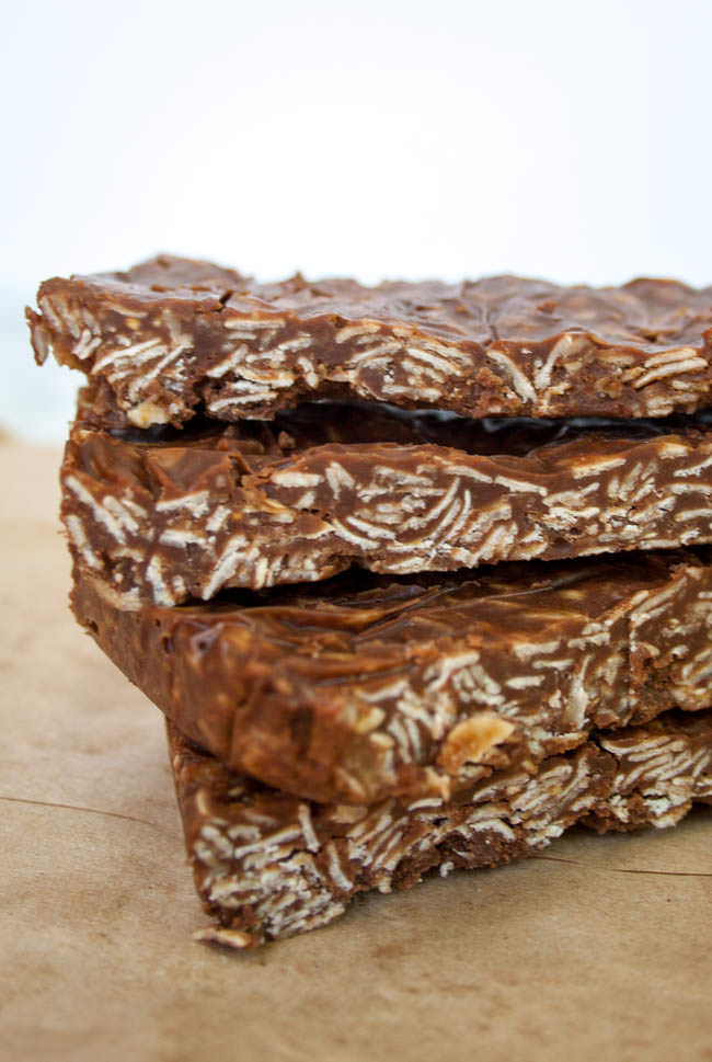 Vegan Chocolate Peanut Butter Granola Bars vertical of four bars stacked on brown paper.