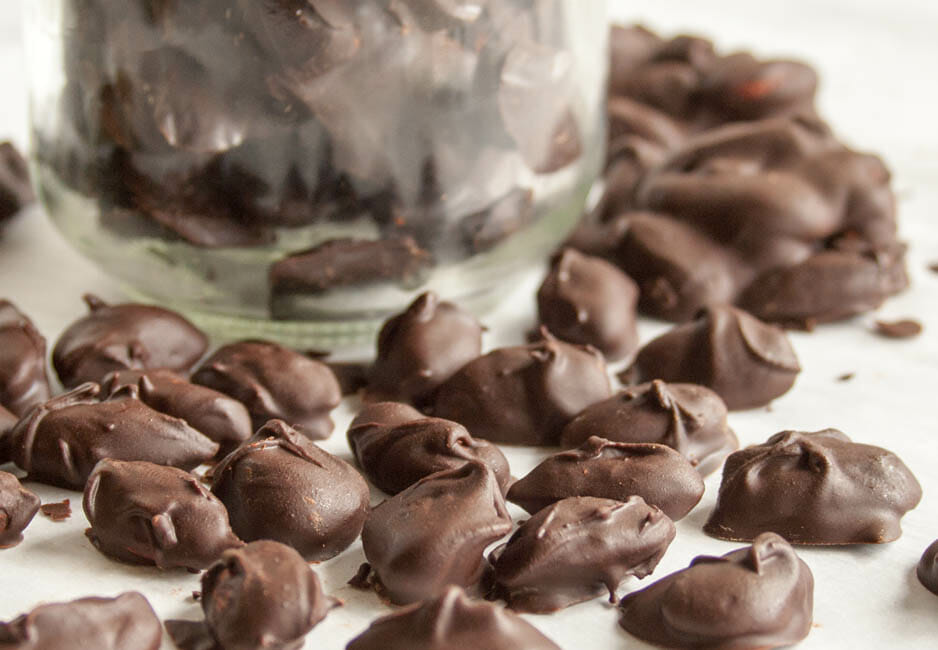 Vegan Mexican Chocolate Covered Almonds close up with jar in the background.