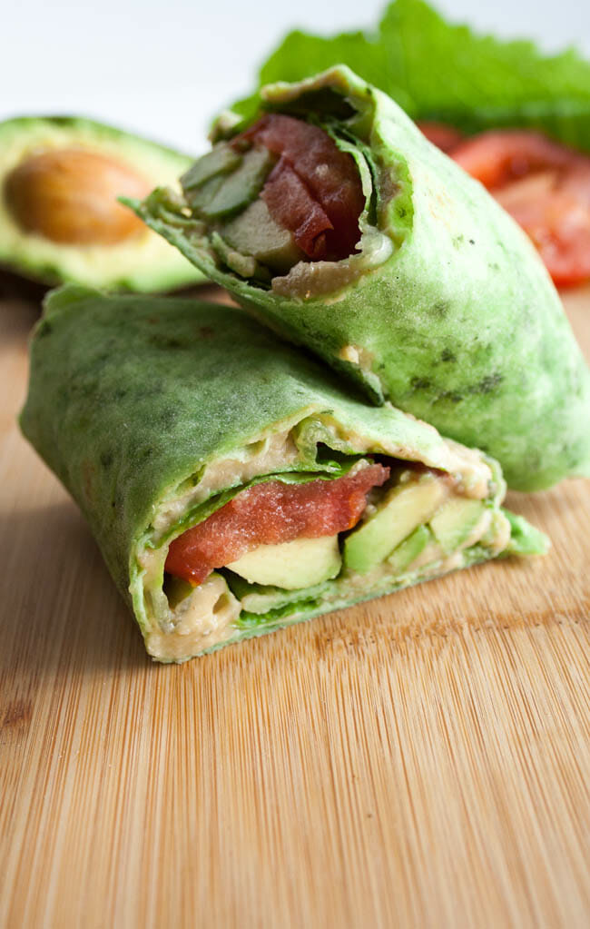 ALT (Avocado, Lettuce, and Tomato) Wrap with avocado, lettuce, and tomato in the background.