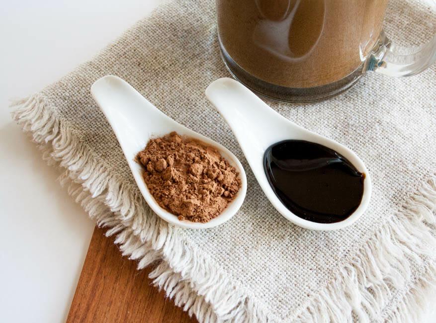 Vegan Molasses Hot Cocoa with close up of cacao powder and blackstrap molasses.