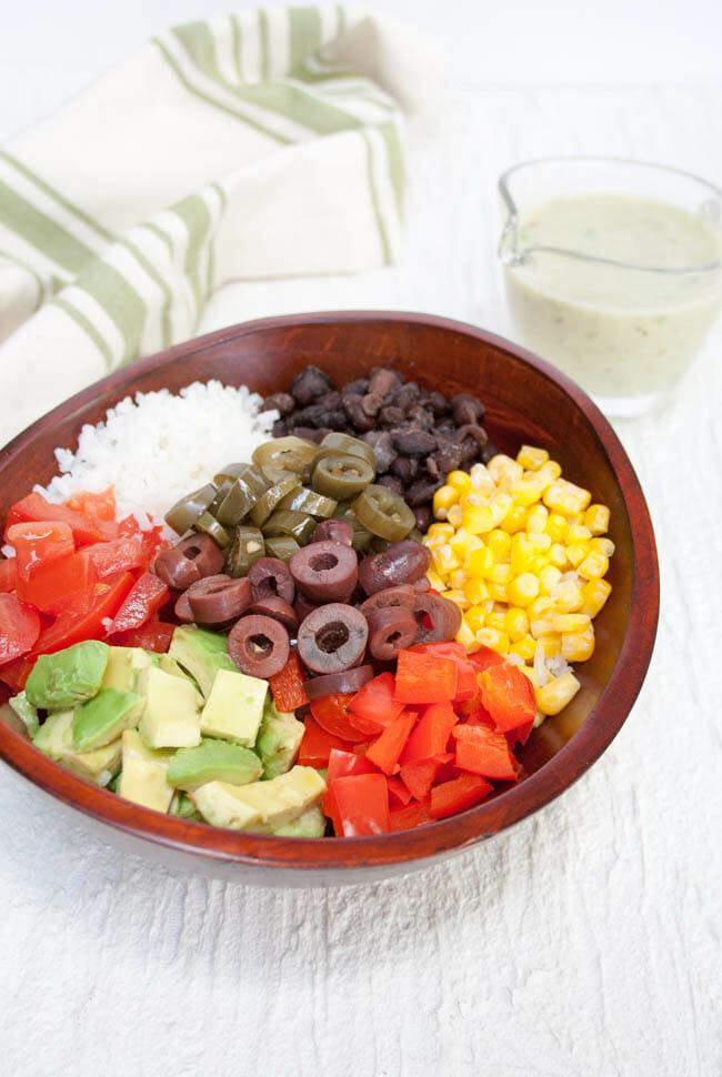 Vegan Burrito Bowl with Creamy Avocado Green Sauce in the background