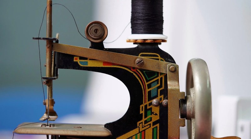 Small hand crank sewing machine as header for fabric face mask pouch pattern post.