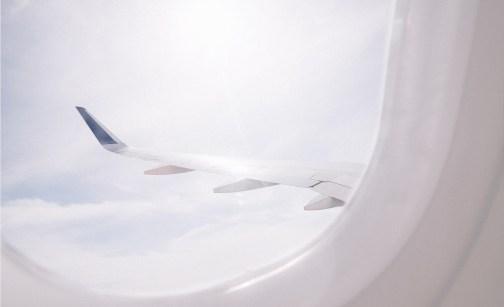 Ailes d'avion à travers un hublot : décollage immédiat vers de nouveaux horizons