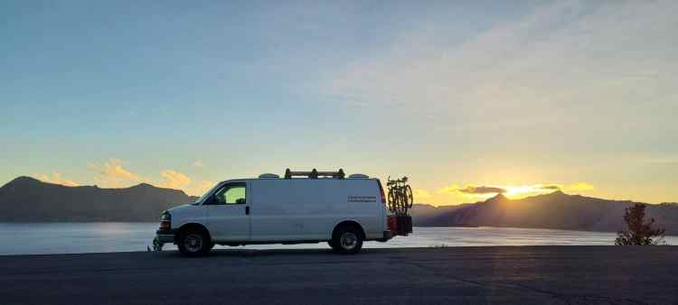 Van in front of sunset at Crater Lake National Park