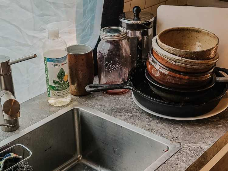 Dishes piled around a sink in a van