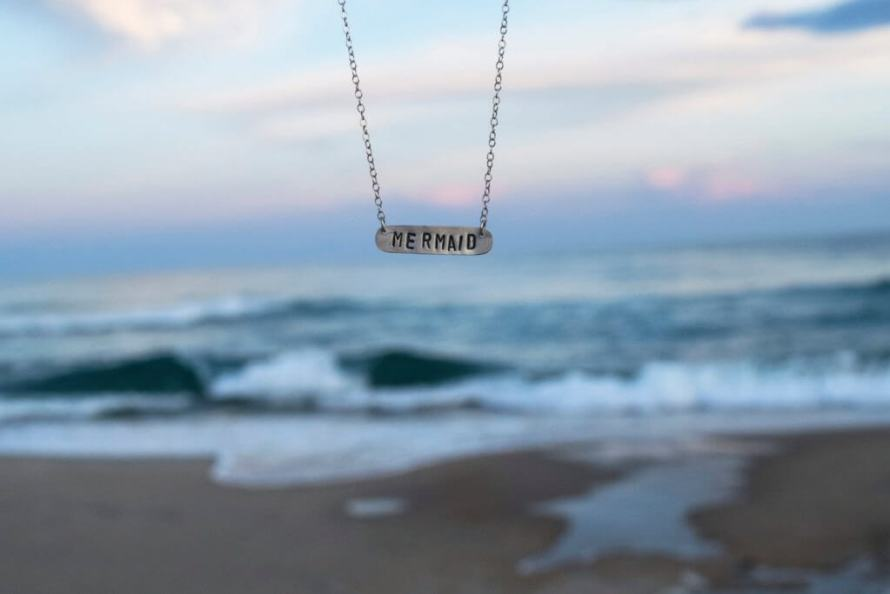 How to Take Better Photos for Your Etsy Shop | Photograph your products in environments that make sense, like this example from LisaChristineShop with their mermaid necklace in front of the ocean.