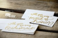 Close up of White Cardstcok with Gold Glitter Embossing: Will You Be My Bridesmaid / Maid of Honor?